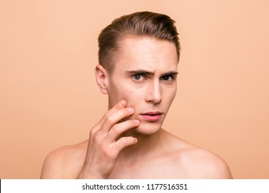 Portrait of frustrated, naked brown-haired man looking for acne on his face isolated on pastel beige background