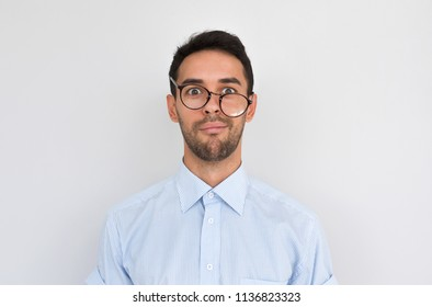 Portrait of frustrated puzzled male with stubble, frowns face, wearing round spectacles posing over white studio background, expresses negative emotion. People, dislike, facial expressions concept
