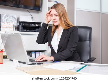 Portrait of frustrated salesgirl working on laptop in showroom