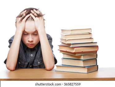Portrait of frustrated schoolboy sitting at a desk with books holding his head having learning problems