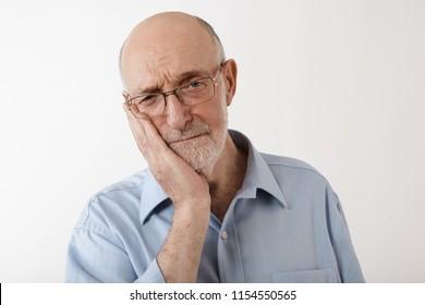 Portrait of frustrated upset mature male in his sixties holding hand on his cheek while suffering from terrible toothache. Retired elderly Caucasian man with gray beard having pain in teeth