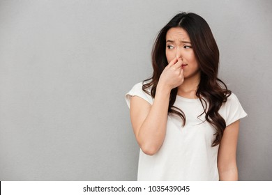 Portrait of frustrated woman 20s pinching nose with disgust on his face due to bad smell isolated over gray background