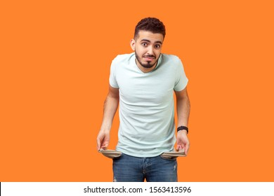 Portrait of frustrated worried brunette man with beard in casual white t-shirt turning out empty pockets showing I have no money gesture, bankrupt. indoor studio shot isolated on orange background