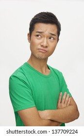 Portrait of frustrated young man, arms crossed, studio shot