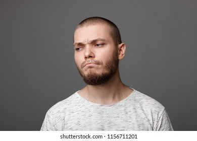 Portrait of frustrated young man on gray background. sadness