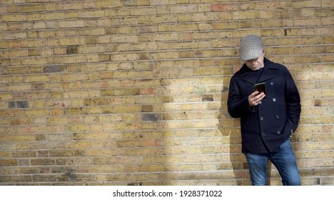 Portrait full body, Handsome good looking, attractive Caucasian man wearing navy blue jacket, jeans and tweed flat cap standing against brick wall, using mobile phone in London, UK