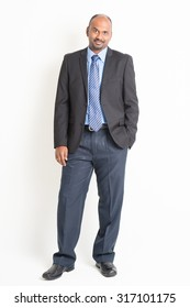 Portrait of full body mature Indian business man arms crossed, standing on plain background.