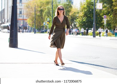 Portrait in full growth, young beautiful blonde woman in dark green dress walking on the street, summer outdoors