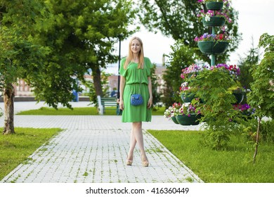 Portrait in full growth, Young beautiful blonde woman in green dress posing outdoors in sunny weather