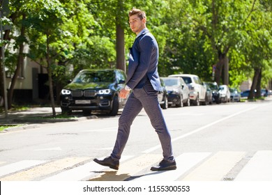 Portrait in full growth of a young man in a business suit crosses the road on a pedestrian crossing