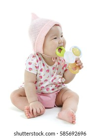 Portrait of full length beautiful Asian baby girl in pink clothes biting teether toy, isolated on white background.