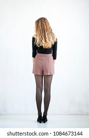 Portrait of a full length curly blonde in a black blouse and short skirt