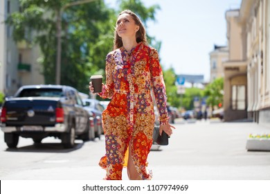 Portrait full length of young beautiful brunette woman in red flowers dress, summer street outdoors