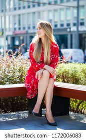 Portrait of a full-length young beautiful blonde woman in a red summer dress, sits on a bench in the city park