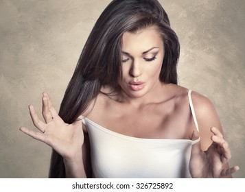 Portrait of fun attractive amazed woman looking down on her breast