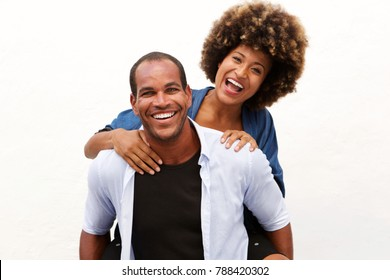 Portrait of fun couple laughing in embrace by white wall