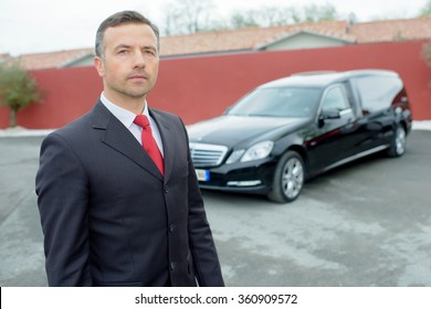 Portrait of funeral director in front of hearse