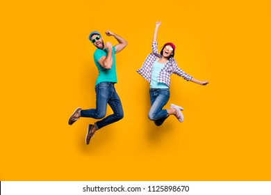 Portrait of funky active couple jumping with raised fists celebrating victory wearing casual clothes isolated on vivid yellow background