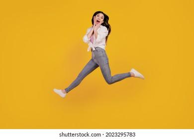 Portrait of funky amazed girl jump plams cheeks run on yellow background