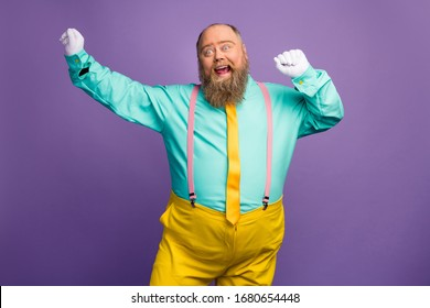 Portrait of funky crazy excited fat overweight man enjoy party discotheque dancing raise fists white gloves wear bright outfit isolated over violet color background