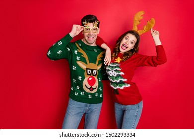 Portrait of funky crazy two people  wife husband in brown antlers costume lean shoulder wear denim seasonal clothes christmas tree design pullover jumper spectacles isolated over red color background