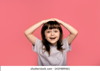 Portrait of funky cute astonished surprised child kid little girl touch hand head shout yell wonder hear incredible information bargain impressed dressed grey clothing isolated pink background