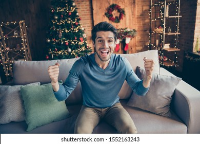 Portrait of funky guy relax sit cozy couch watch final world soccer cup match support team on newyear christmas eve scream yeah in house with x-mas fairy decoration toys illumination