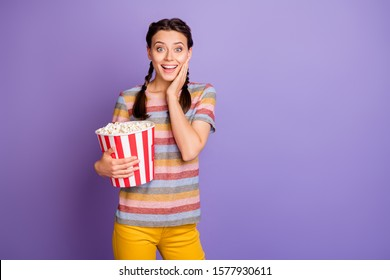 Portrait of funky teen youngster girl watch funny movie hold big pop corn box  impressed scream wow omg touch hand face wear yellow millennial outfit isolated over purple color background