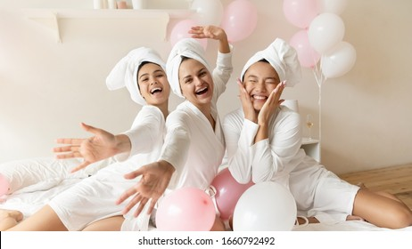 Portrait funny Asian bride with bridesmaids sitting on bed in soa or hotel, having fun at hen party, three happy beautiful young women wearing white bathrobes and towels on head looking at camera