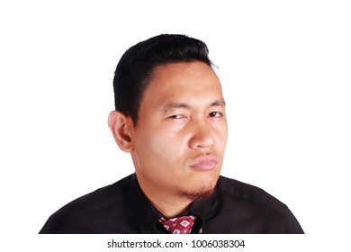 Portrait of funny Asian businessman showing cynical angry facial expression, isolated on white