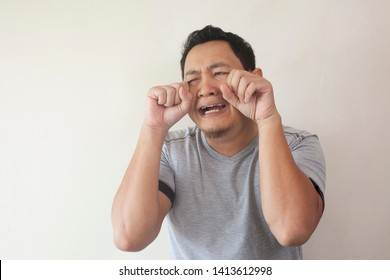 Portrait of funny Asian man crying close his eyes, sad depression frustration hopeless expression