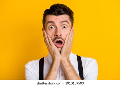 Portrait of funny attractive worried guy wearing white shirt unexpected news reaction isolated over bright yellow color background