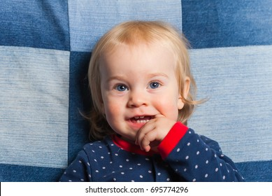 portrait funny baby boy with finger in mouth