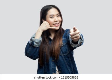 Portrait of funny beautiful brunette asian girl in casual blue denim jacket makeup standing with call gesture, looking and pointing at camera. indoor studio shot, isolated on light grey background.
