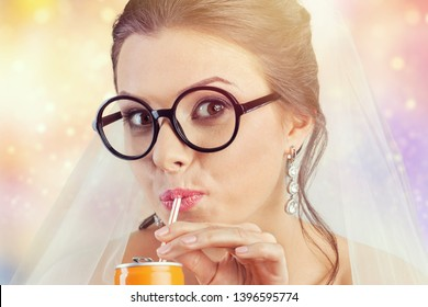 Portrait of a funny beautiful hipster bride drinking something from tin can through plastic sipper. Daylight. Hipster style. Black and white (monochrome) studio shot