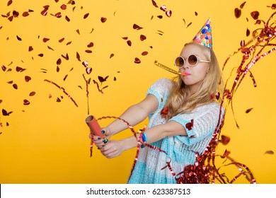 portrait of funny blond woman in birthday hat and blue shirt and red confetti on yellow background. Celebration and party. Having fun.