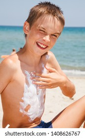 Portrait of funny boy sitting on a beach during summer vacation applying abundance of sunblock cream on his chest, sea water is seen in background