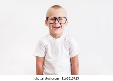 Portrait of funny boy smiles with big black glasses on a white background