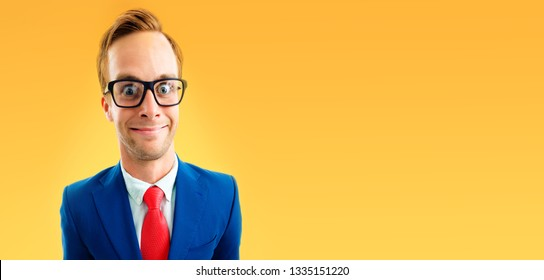 Portrait of funny businessman in glasses, blue confident suit and red tie, with copy space area for some text, advertising or slogan, over yellow-orange color background.