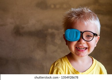 Portrait of funny child in new glasses with patch for correcting squint 