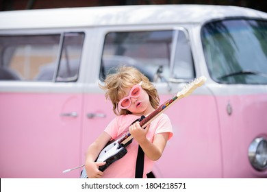 Portrait of a funny child with pink glasses practicing a song during a guitar lesson on street. Music concept, kids music school. Rock concert