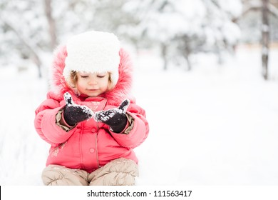 Portrait of funny child in winter against snow background