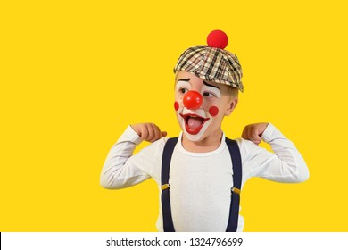 Portrait funny child.Cheerful boy,costume clown,red nose,makeup.Emotional face little comic kid.Happy baby isolated yellow background.1 April fool's day celebration. concept birthday, holiday, humor.