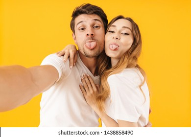 Portrait of funny couple man and woman in basic t-shirts sticking out tongues together while taking selfie photo isolated over yellow background