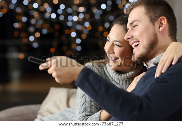 Portrait of a funny couple watching tv sitting on a couch in the living room at home in a winter night