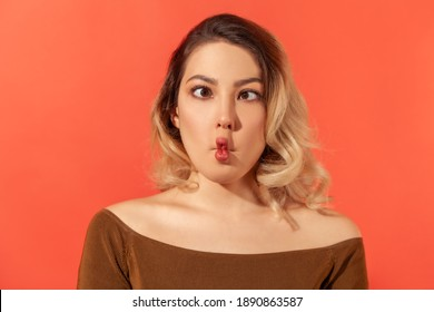 Portrait of funny crazy young beautiful blonde womanl in brown blouse standing and looking with crossed eyes and fish lips. Indoor studio shot isolated on red background