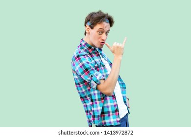 Portrait of funny crazy young man in casual blue checkered shirt and headband standing with smoke gesture hand on his lips and looking at camera. indoor studio shot, isolated on light green background