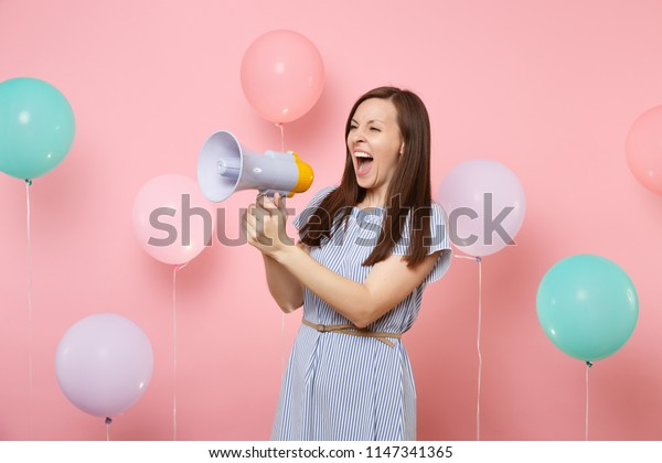 Portrait of funny crazy young pretty woman wearing blue dress holding megaphone screaming on pastel pink background with colorful air baloons. Birthday holiday party, people sincere emotions concept