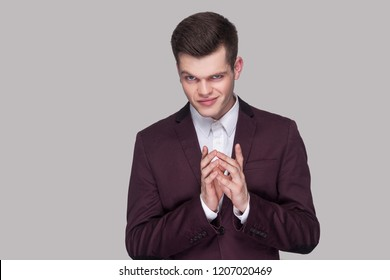 Portrait of funny cunning handsome young man in violet suit and white shirt, standing, looking at camera with cheating face. indoor studio shot, isolated on grey background.