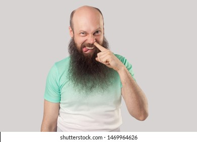 Portrait of funny dirty middle aged bald man with long beard in light green t-shirt standing drilling with finger on his nose, tongue out and looking. indoor studio shot, isolated on grey background.